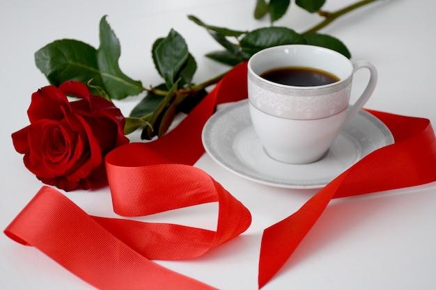 Rode roos, rode streep, kopje koffie op plaat, grijze theeset op witte tafel. valentijnsdag traktatie