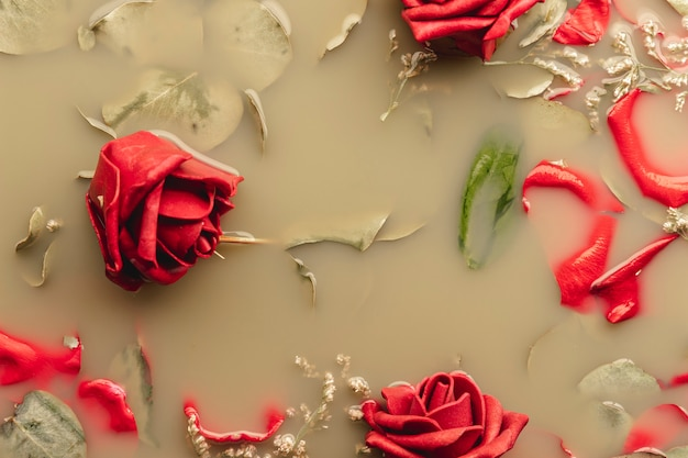Rode rozen en bloemblaadjes in bruin water