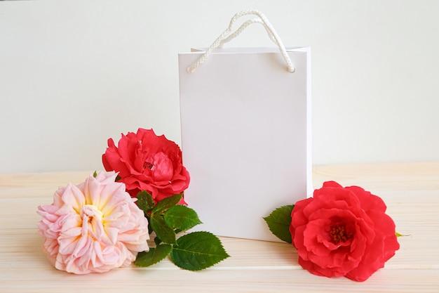 Rode rozen en cadeauzakje. plaats voor inscriptie op de verpakking.