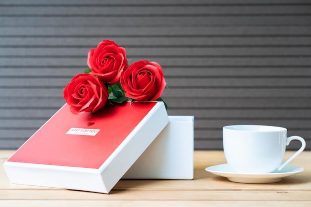 Rode rozen en geschenkdoos op hout