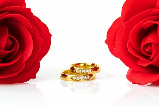 Rode rozen en gouden ringen op wit
