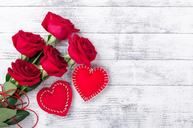 Rode rozen en handgemaakte harten op houten witte achtergrond. het concept van valentijnsdag. kopieer ruimte voor uw tekst