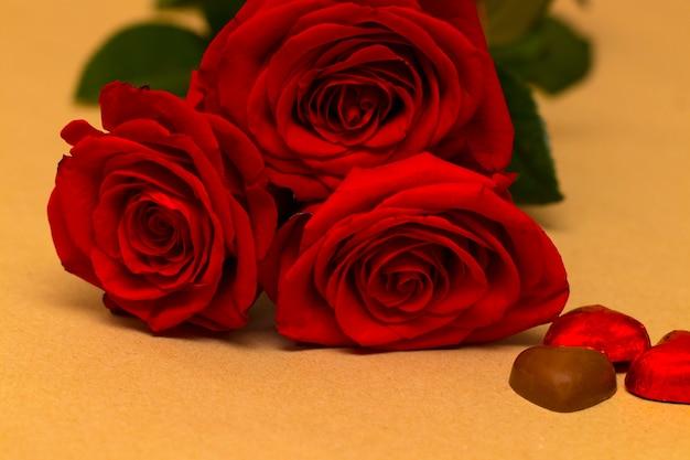 Rode rozen en harten op een gele achtergrond. valentijnsdag achtergrond