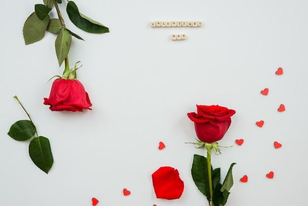Rode rozen en hartvormornamenten op witte achtergrond