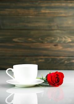 Rode rozen en koffiekopje op tafel met kopie ruimte, valentijnsdag concept met rode rozen