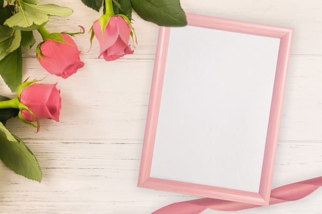 Rode rozen en lichte houten achtergrond met roze frame voor valentijnsdag