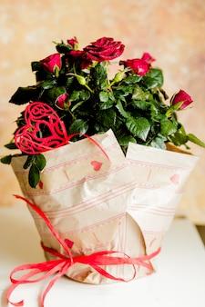Rode rozen in ambachtelijk papier. cadeau voor verjaardag of valentijnsdag. bloemen in een pot versierd met een hart. bloemen cadeau voor een bruiloft.