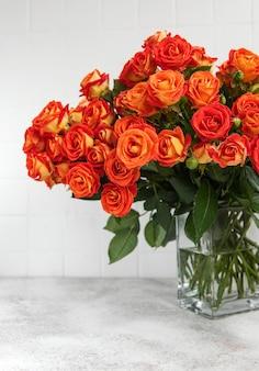 Rode rozen in een glazen vaas op tafel
