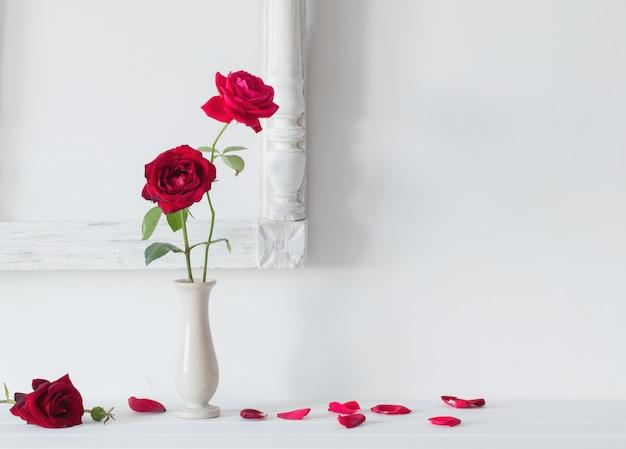 Rode rozen in een vaas op ruimte witte muur