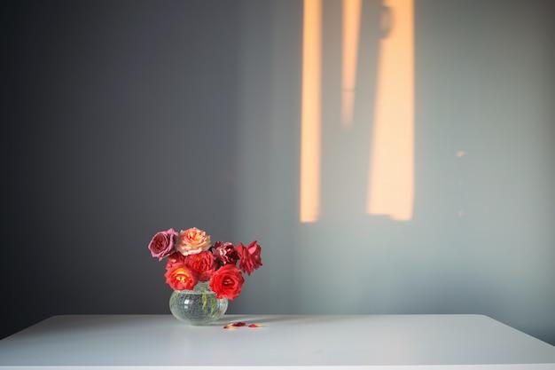 Rode rozen in glazen vaas op grijze achtergrond