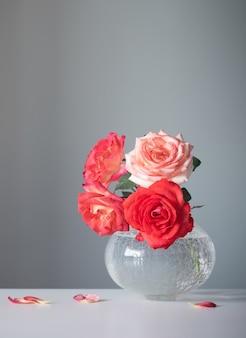 Rode rozen in witte vaas op grijze achtergrond