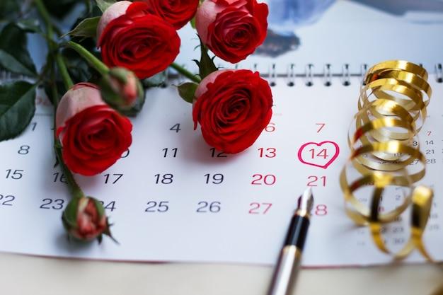 Rode rozen liggen op de kalender, 14 februari, valentijnsdag