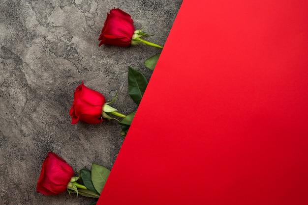 Rode rozen liggen prachtig op een grijze en rode achtergrond.