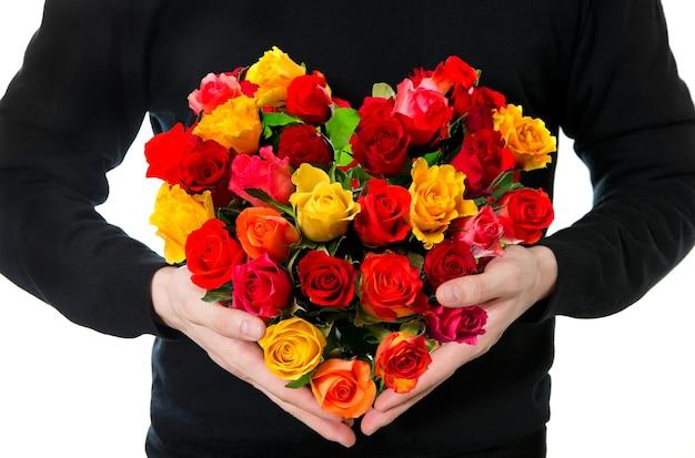 Rode rozen. man's handen met kleurrijk bloemenboeket in hartvorm