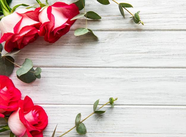 Rode rozen met de dagachtergrond van de eucalyptusvalentijnskaart