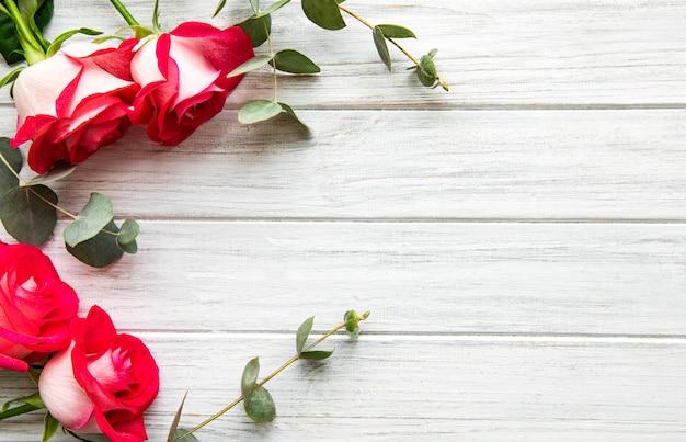 Rode rozen met eucalyptus op houten achtergrond