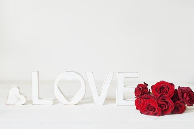 Rode rozen met hart, houten letters liefde, briefkaartsjabloon