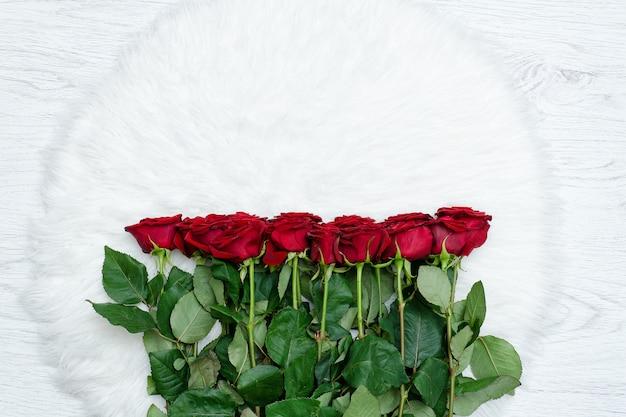 Rode rozen op een wit kunstbont, bovenaanzicht