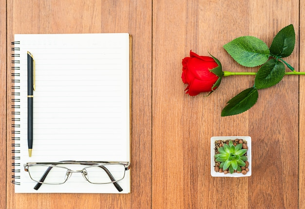 Rode rozen op houten tafel en kladblok
