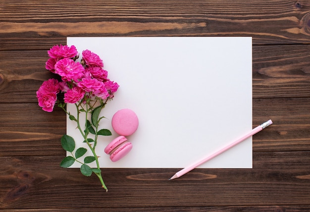 Rode rozen potlood en blanco papier kaart op houten achtergrond
