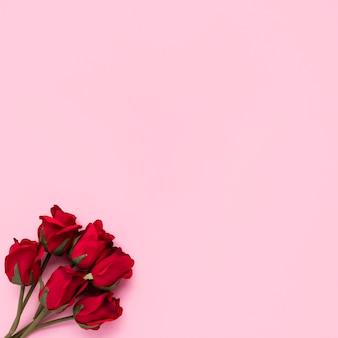 Rode rozen takken op roze tafel