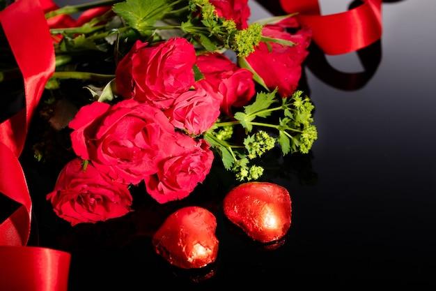 Rode rozenboeket en hartvormige chocolaatjes, rood lint op een zwarte achtergrond