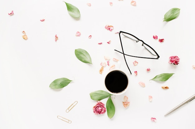 Rode rozenknop, glazen, bladeren, koffie op wit oppervlak