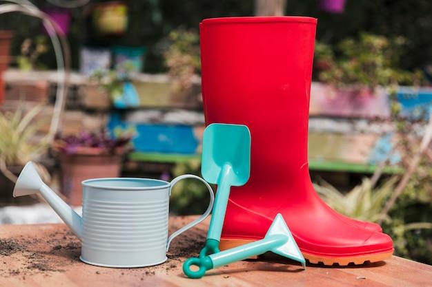 Rode rubberen laars; blauwe schop en gieter op tafel in de tuin