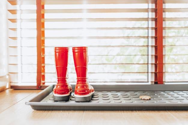 Rode rubberen schoenen voor kinderen in de hal van het huis. felrode tuinlaarzen. regenachtige schoenen. herfst, lente kinderen laarzen concept.