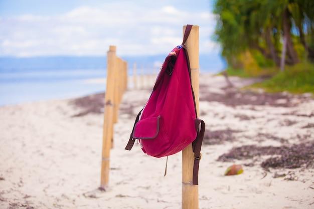 Rode rugzak op het hek op verlaten tropisch eiland