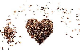 Rode ruwe rijst, ongepelde rijst en gemengde korrels in een hartvorm, gezond concept, conc Valentine