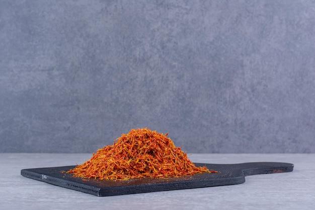 Rode saffraan zaden geïsoleerd op een houten schotel. hoge kwaliteit foto