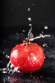 Rode sapgranaatappel op donkere lijst. handige granaatappel