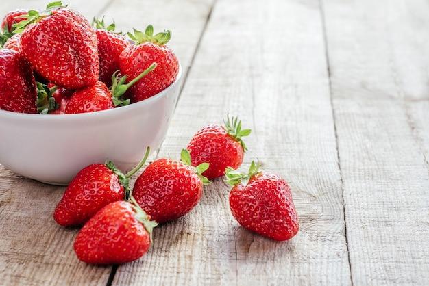 Rode sappige aardbeien in een kom op houten tafel met kopieerruimte, zomerfruit met antioxidanten, vitamine c, mangaan, foliumzuur en kalium