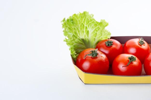 Rode sappige tomaten in een milieuvriendelijke verpakking of container versierd met een blaadje sla op een witte geïsoleerde achtergrond. het concept van milieuvriendelijke verpakkingen en biologische producten. ruimte voor tekst