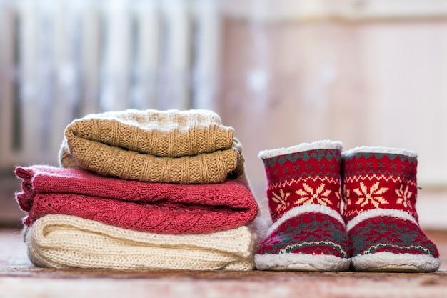 Rode schoenen met nieuwjaarspatroon en een stapel gebreide truien
