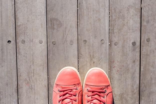 Rode schoenen op een oude houten plank achtergrond