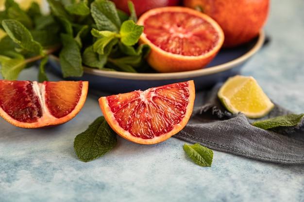 Rode siciliaanse sinaasappelen met limoenen en munt op blauwe ondergrond