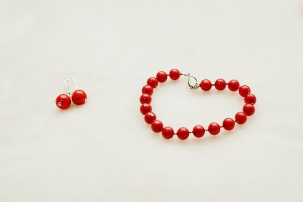 Rode sieraden: armband en oorbellen met kralen op een witte achtergrond