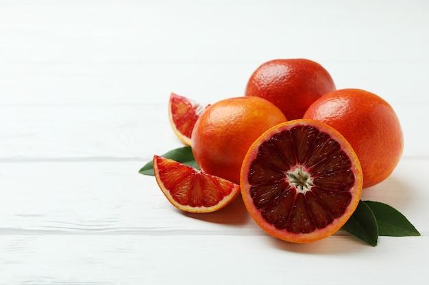 Rode sinaasappelen en bladeren op witte houten tafel, ruimte voor tekst