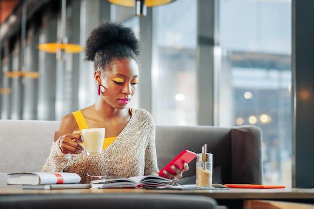 Rode smartphone drukke aantrekkelijke ijverige student die haar rode smartphone vasthoudt terwijl ze koffie drinkt