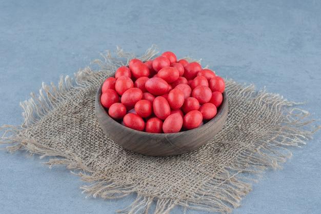 Rode snoepjes in de beker op de onderzetter, op de marmeren tafel.