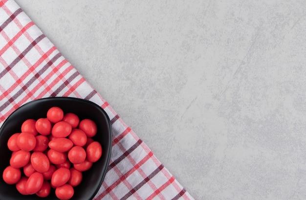 Rode snoepjes in de darm op de handdoek op het marmeren oppervlak