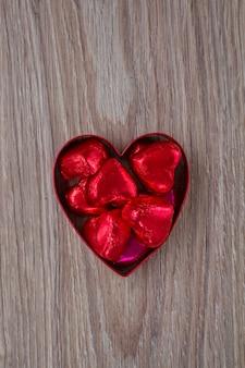 Rode snoepjes in hart op houten tafel