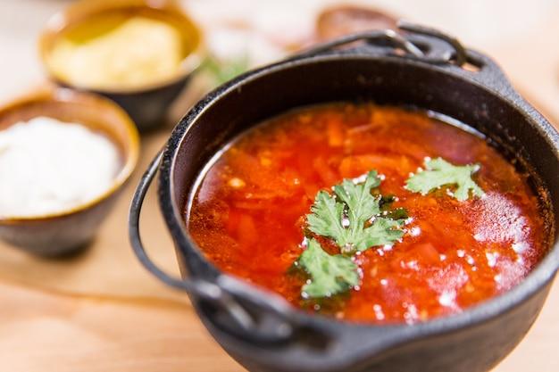 Rode soep in zwarte kom op houten lijst in een restaurant. gezond eten