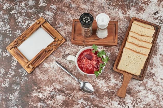 Rode soep met kruiden geserveerd met brood, bovenaanzicht.