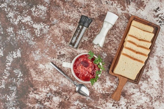 Rode soep met sneetjes brood en kruiden.