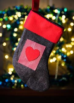 Rode sok met hart tussen kerstverlichting en kleurrijke versieringen op de achtergrond