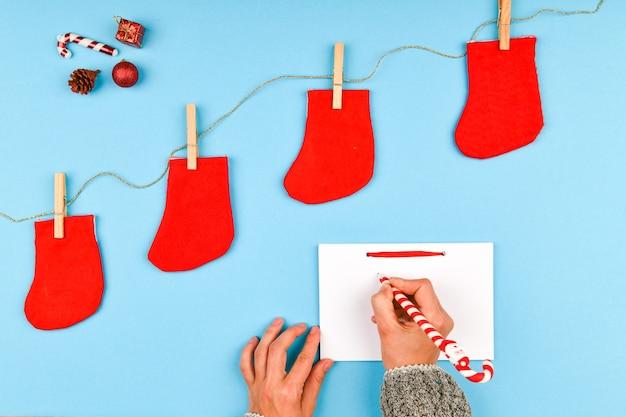 Rode sokken op een wasknijper. op een blauwe ruimte. een leeg notitieboekje met een stel. uitzicht van boven. opknoping op waslijn met wasknijpers op een blauwe ruimte. nieuwjaar concept.