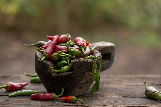 Rode spaanse pepers en groene spaanse pepers op houten lijst